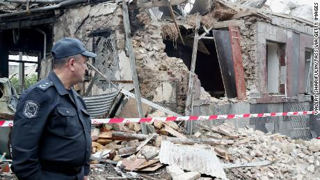 A policeman stands in front of a building damaged by shellfire.