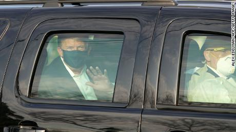 US President Trump waves from the back of a car in a motorcade outside of Walter Reed Medical Center in Bethesda, Maryland on October 4, 2020.