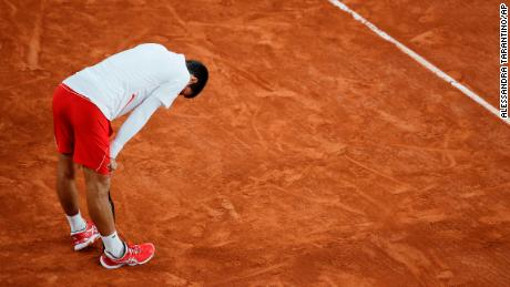 Djokovic leans on his racket in the quarterfinal match against Carreno Busta.