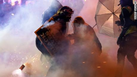 Protesters retreat after police used tear gas Friday, Oct. 9, 2020, in Wauwatosa, Wisconsin.