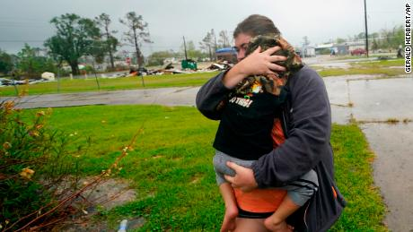 Danielle Fontenot runs to a relative's home in the rain with her son Hunter ahead of Hurricane Delta, Friday, Oct. 9, 2020, in Lake Charles, Louisiana.