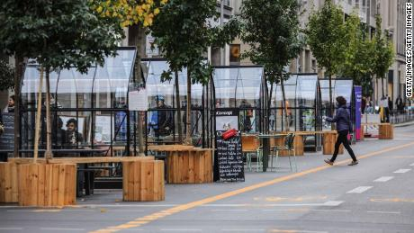 Mostly empty seating areas outside a coffee shop at Friedrichstraße in Berlin on Friday, with the city facing new rules.