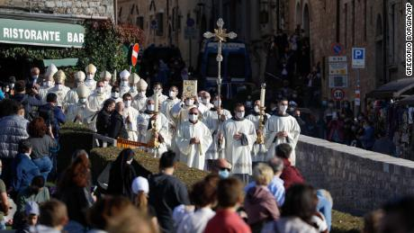 A procession passes through the streets of Assisi, Italy before the beaten ceremony of 15-year-old Carlo Acutis.
