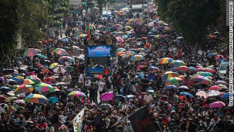 Protesters seen walking toward Government House during an anti-government demonstration in Bangkok.