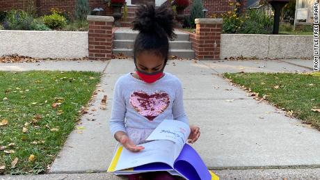 A child reading one of the books from a Little Free Library.
