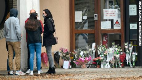 People stand next to flowers displayed at the entrance of the school in Conflans-Sainte-Honorine.
