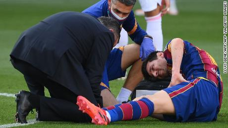 Messi receives medical attention after being tackled during the game against Real Madrid.