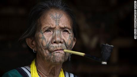 This photo taken on March 3, 2020 shows a tattooed Chin ethnic woman smoking at her house in a village of Chin State, western Myanmar.