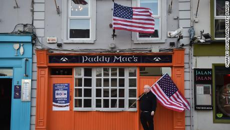 Paddy Macs bar owner Michael Carr stands outside his pub with an American flag on November 7, 2020.