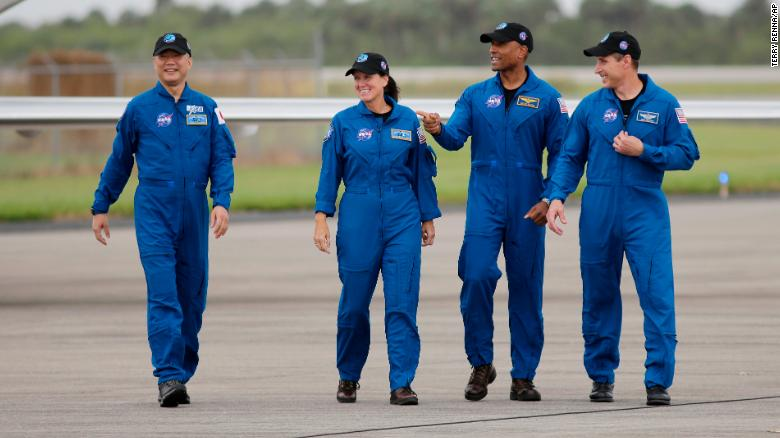From left to right, astronauts Soichi Noguchi, Shannon Walker, Victor Glover and Michael Hopkins walk to the microphone at the Kennedy Space Center on Sunday.