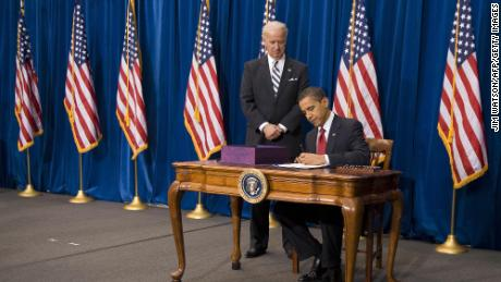 Then Vice President Joe Biden stands with President Barack Obama as he signs $787 billion stimulus package in February 2009.