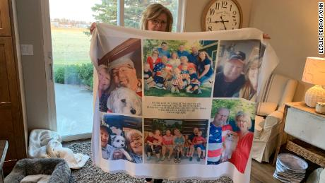 Chris Bjorkman holds a quilt with pictures of her late husband.