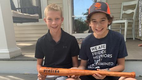 Tommy Rhomberg, right, and Walker Viessman hold the bat Tommy made for Walker.