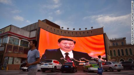 This photo taken on June 4, 2019, at the end of Ramadan, shows people walking past a screen showing images of Chinese President Xi Jinping in Kashgar, in China's western Xinjiang region.