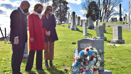 Mark Kelly, who will be sworn in as a US senator on Wednesday, and his wife, former Rep. Gabby Giffords, visit the gravesite of the late Sen. John McCain in Annapolis, Maryland, on Tuesday.