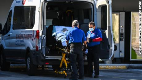 Medics earlier this month transfer a patient on a stretcher from an ambulance outside of emergency at Coral Gables Hospital where coronavirus patients are treated near Miami.