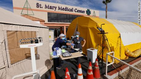 Emergency room tech Brenda de la Cruz registered nurse Janet Hays work on Dec. 8 outside St. Mary Medical Center in Apple Valley, California. The triage tents handle the overflow of patients.