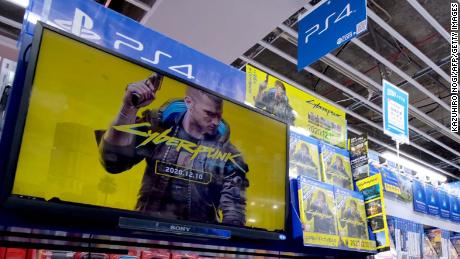 """A screen shows a promotional video for """"Cyberpunk 2077"""" in a store in Tokyo. Physical copies are still being sold."""