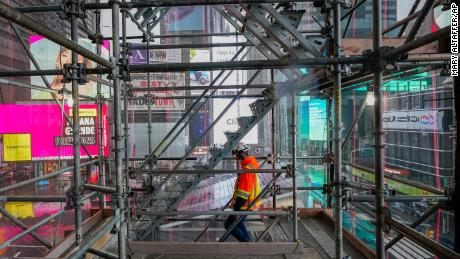 A construction worker walks down a staircase in the scaffolding of TSX Broadway under construction, Thursday, Oct. 29, 2020, in New York's, Times Square.