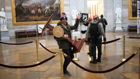 A pro-Trump protester carries the lectern of U.S. Speaker of the House Nancy Pelosi through the Roturnda of the U.S. Capitol Building.