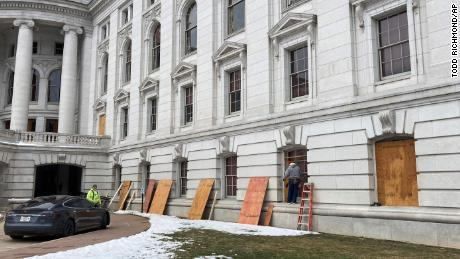 Workers begin boarding up the Wisconsin state Capitol building in Madison on Monday.
