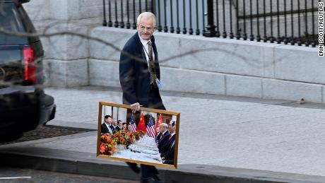 White House advisor Peter Navarro leaves the West Wing of the White House with a photograph of U.S. President Donald Trump and Chinese President Xi Jinping, in Washington, U.S., January 13, 2021.