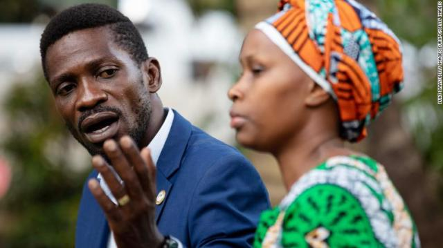 Bobi Wine, left, addresses the media with his wife, Barbara Itungo Kyagulanyi, as security forces surround his home on Friday in Kampala, Uganda.