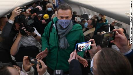 On Sunday, passengers and journalists take a photo of Alexey Navalny as soon as he takes his seat on the flight.