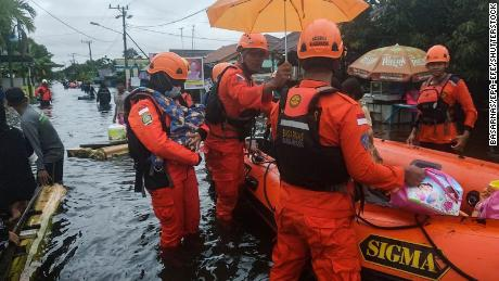 Rescuers evacuate people from a flooded residential area in Banjarbaru, South Kalimantan, Borneo Island, on 17 January 2021.