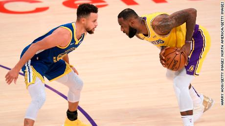 LeBron James is protected by Stephen Curry on Monday.
