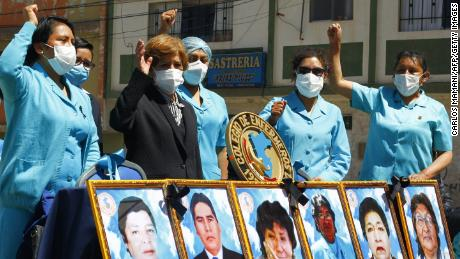 Health workers in the highland city of Puno in the Andes, protest with pictures of their co-workers who died during the pandemic in August.