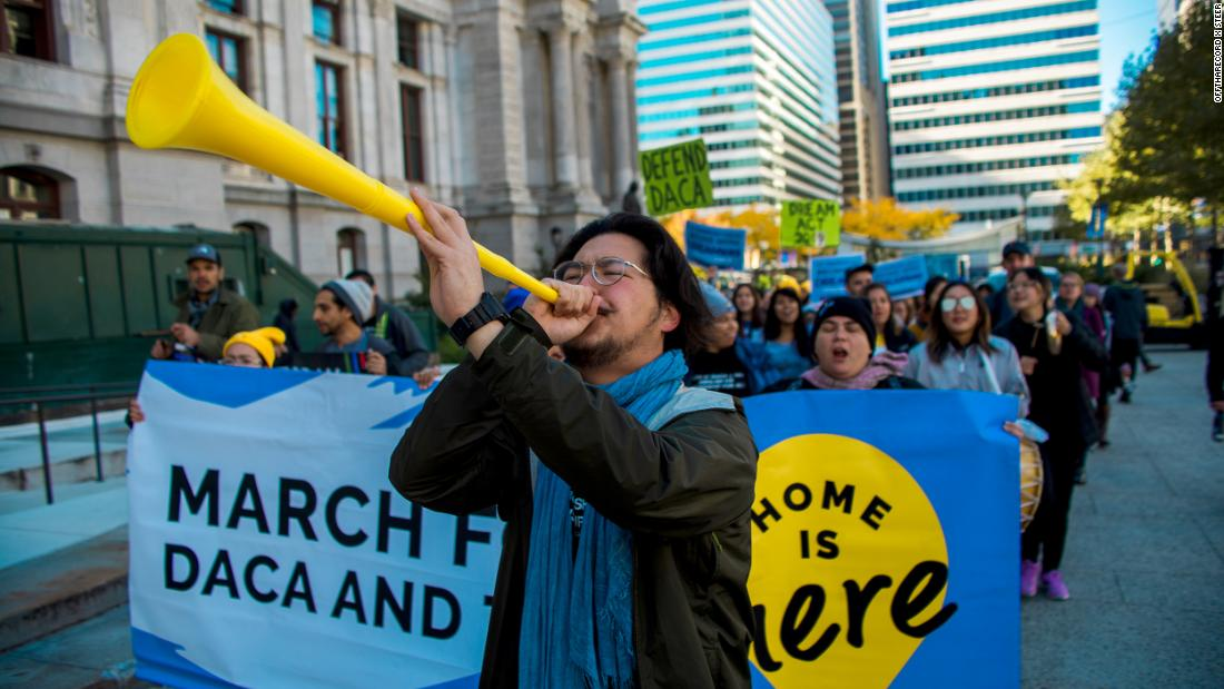 Glo Harn Choi, shown here leading a protest march in 2019, says years of physical labor have taken a toll on his mom.