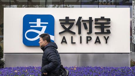 A pedestrian walks past an Alipay sign outside an Ant Group Co. office building in Shanghai, China, on Thursday, Dec. 24, 2020.