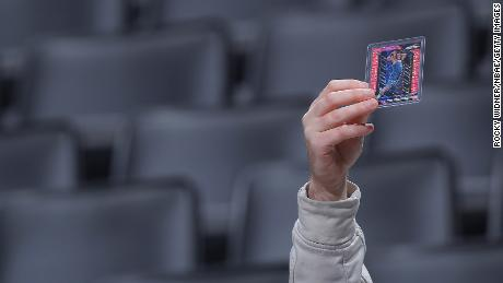 A fan holds the trading cards of the Minnesota Timberwells before a game on February 3, 2020.