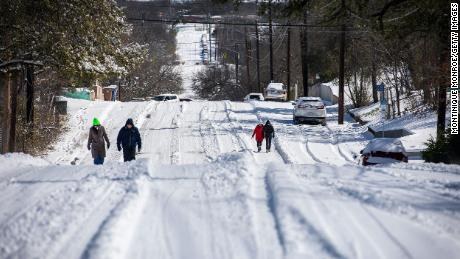 Pedestrians walk on an icy road on Monday, February 15, in East Austin, Texas.