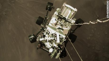 """This shot from a camera on Perservance's """"jetpack"""" captures the rover in midair, just before its wheels touched down."""