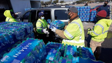 Water is loaded into a vehicle at a City of Houston water distribution site Friday in Houston. The drive-thru stadium location provided bottled water to individuals in need while the city remains on a boil water notice.