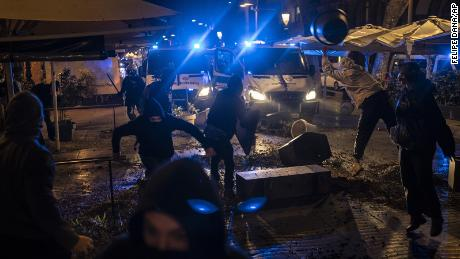 Demonstrators throw objects towards police during a protest condemning the arrest of repper Pablo Hasél in Barcelona on Friday