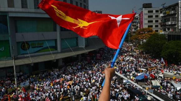 A protester waves the National League for Democracy (NLD) flag while others take part in a demonstration against the military coup in Yangon on February 22.