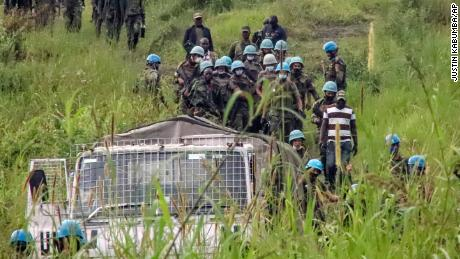 United Nations peacekeepers remove bodies from the attack area in North Kivu province on Monday.