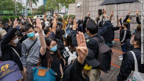 Pro-democracy activists gesture as they line up outside the West Kowloon court in support of the arrested activists.