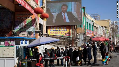 Residents walk through a security checkpoint and past a screen showing Chinese President Xi Jinping in Hotan, Xinjiang, on November 3, 2017.