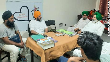 Singh, second from left, sits with volunteers at Pind California, a shelter set up for protestors at Delhi's Tikri border.