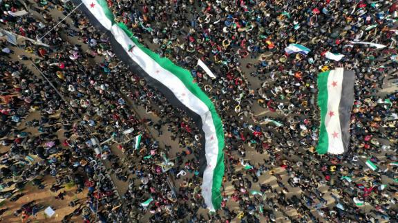 An aerial picture shows Syrians waving the national flag during a gathering in the rebel-held city of Idlib on March 15, 2021, as they mark 10 years since the nationwide anti-government protests that sparked the country's devastating civil war.