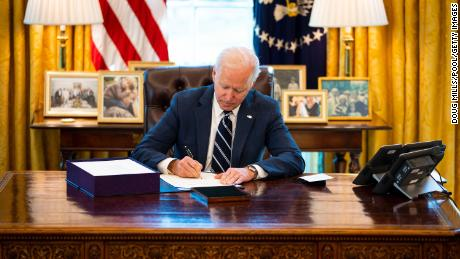 President Joe Biden signs  the $1.9 trillion Covid relief bill into law in the Oval Office of the White House on Thursday, March 11, in Washington