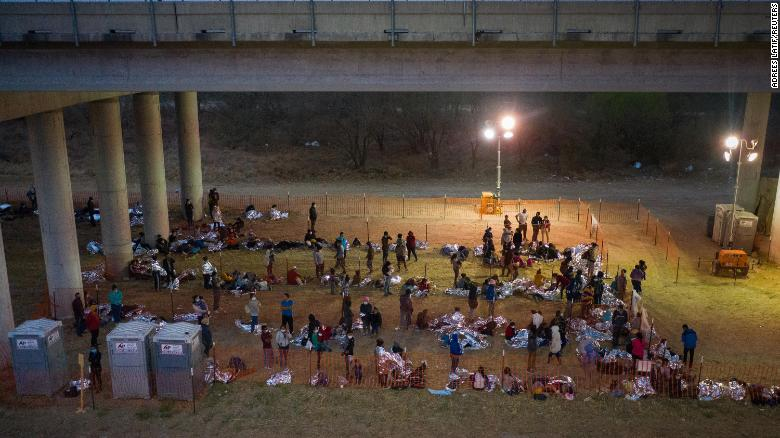 Asylum seeking migrant families and unaccompanied minors from Central America take refuge in a makeshift U.S. Customs and Border Protection processing center under the Anzalduas International Bridge after crossing the Rio Grande river into the United States from Mexico in Granjeno, Texas, U.S., March 12, 2021.