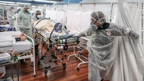 Medical staff transport a patient on a stretcher at a field hospital as coronavirus cases soar on March 11, 2021 in Santo Andre, Brazil.