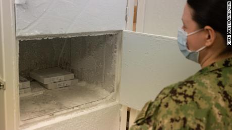 Lieutenant Jennifer M.  White opens the freezer used to store the Pfizer vaccine at the Naval Medical Center Portsmouth on 15 March.