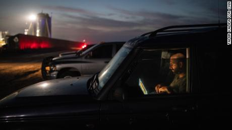 Jack Beyer edits photographs in his vehicle near the SpaceX launch site.
