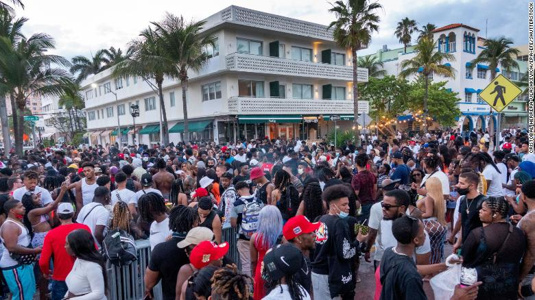 A large crowd of people gathers on a walkway near the beach in Miami Beach on Saturday.